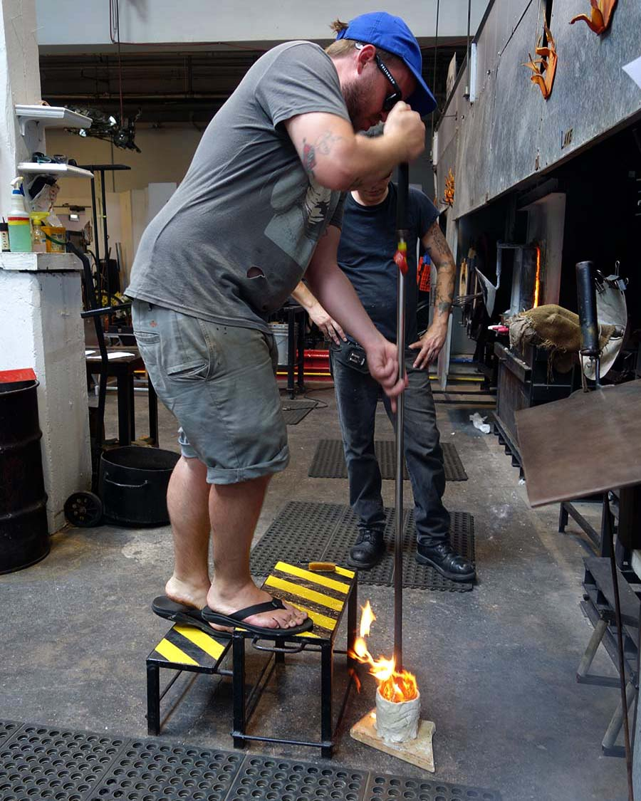 "alt=""Glassblower Kyle Herr tests the mold"""