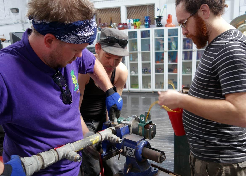 "alt=""Resident glassblower, Kyle Herr, and technicians, Drake Fuller and Zachary LeBlanc, replace the solenoid valve"""