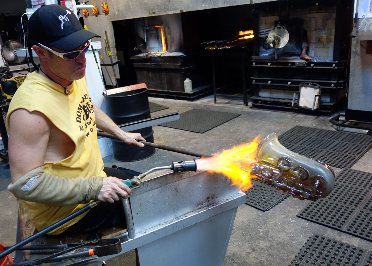 "alt=""Master glassblower Robert Stern torches the blowpipe"""