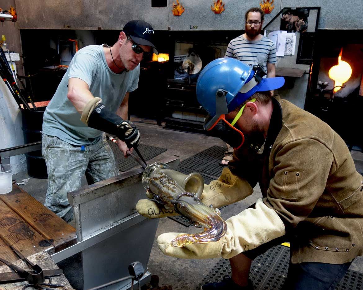 "alt=""Resident glassblower Kyle Herr helps Robert Stern in initiating the crack-off"""